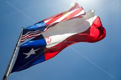 Creative view from below of the mighty U.S. and Texas flags flying in the breeze of the Lone Star State.