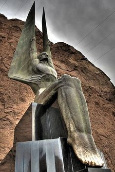 Hoover Dam angel statue. I've been there. The feet are rubbed gold because it is said if you rub the feet you'll have good luck
