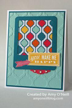 Supplies Used: Stamps: Hello, Lovely Ink: Daffodil Delight, Strawberry Slush Paper: Pool Party, Island Indigo, Strawberry Slush, Whisper White, Quatrefancy Specialty dsp Embellishments: Squares Framelits, 3/16″ Corner punch, Modern Mosaic embossing folder, Artisan Label punch, Rhinestone Basic Jewels card by Amy O'Neill