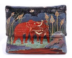"""The LOTUS rattan clutch bag, has been a signature piece of Lotus Arts de Vivre for over 20 years. For this new version a prominent Balinese artist was engaged to paint the art-work."