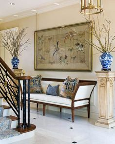 A Chinese silk embroidery hangs above a settee in the entry, where a new marble-and-granite floor wraps into the conservatory and sunroom.