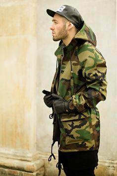 Mann trägt ein Outfit mit Camouflage Jacke