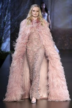 Rose gold Chantilly lace gown with crystal and glass bead hand embellishment. Ostrich feather and fox fur cape.