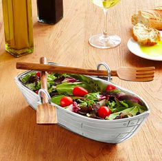 A rowboat dish complete with serving utensil oars.