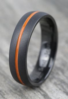 This 6 mm Orange Antiqued Men's Wedding Ring in Zirconium band features a grooved center with orange antiquing and beadblasted edges for a unique look. Proudly made in the USA and comfort fit.