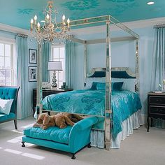 Hollywood Glamour   Touches of basic black and black-and-silver furniture mix with fabrics in shades of aqua and teal. The mirrored canopy bed features a headboard upholstered in deep turquoise velvet. The opulent floral silk of the duvet cover inspired the bold ceiling color.