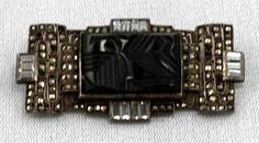 German Art Deco sterling brooch, done with a geometric carved black onyx center accented with glass baguettes and studded with marcasites ~ circa 1920.