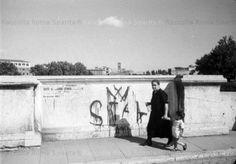 1945 Una donna cammina lungo Ponte Cestio tenendo per mano un bambino. Sullo sfondo appena visible l'isola Tiberina