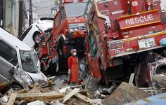 Tomoko Yagi looks at two firetrucks that were tossed around like toys in the tsunami in Kamaishi, Iwate prefecture, on March 20.