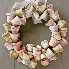 Terra-cotta Pots | Warm up an entry with earthy terra-cotta rooting pots. Use weathered pots from your own collection, or age new ones using our technique. Hide the wreath hanger with a ribbon, and then add a bow. | SouthernLiving.com