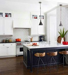 Contrast is key here. White cabinetry and counter tops paired with dark hardwood floors, navy blue table and counter drawers paired with grey tones, and gold stools.