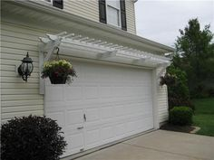 Garage door pergola with hanging planters.