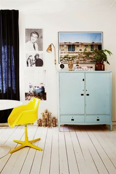 A Swedish vintage inspired house. White floorboards, mint green industrial style cupboard, canary yellow swivel chair