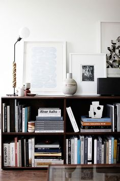Old and traditional bookcase styled with modern lamp and posters.