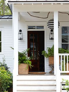 This farmhouse porch beckons you in and extends a warm, yet fresh, welcome, thanks to its punchy black accessories, white facade and gorgeous plantings. Secret to Pretty: Plenty of greenery, proving that plants don't have to be colorful to be impactful. Here, greenery pops against the porch's clean white surfaces creating a modern farmhouse vibe./