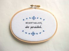 "Completed cross stitch of the the phrase ""Nevertheless, she persisted' "" framed in 3x5"" natural wood embroidery hoop frame."