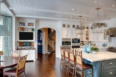A painted Nantucket beadboard ceiling, dropped beams and black walnut floor planks of random width complete the classic look in this kitchen.