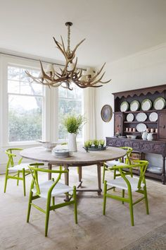 Inspired by the lush landscape just outside the windows (which were salvaged from an old train depot!), the homeowner of this 105-year-old Victorian farmhouse filled the dining room with rustic wood elements and pops of green. The Beech wishbone chairs, which are lacquered in an apple green, pop against the large antique hutch that stores the homeowner's collection of copper Moscow mule mugs and green and white china. A pale pink Oriental rug with subtle hints of sky blue and chartreuse roun...