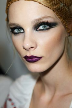 Purple plum lips, heavy winged liner, light and very natural brows, dramatic false lashes.