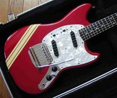 An electric guitar with a racing stripe. (In this case a 1972 Fender Mustang)