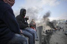 Demonstran Palestina duduk di atas tembok penghalang kontroversial Israel yang memisahkan kota Abu Dis dan Yerusalem di Tepi Barat.