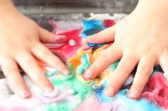 childs hands in baking soda, vinegar and food colouring