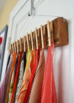 Use repurposed wood and a few clothes pins to make this scarf organizer. #organizecloset