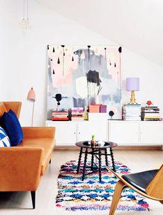 Lavendar walls, camel color sofa and colorful boucherite rug. Great color scheme for a kids' room.