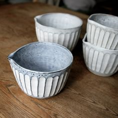 Faceted pouring bowls Slab coil built in white stoneware decorated with black slip under a frost white glaze Varying sizes from 15cm in height 2014
