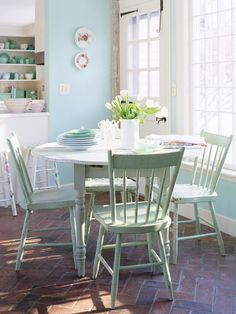 A white table and green chairs create a cottage-chic eating area.