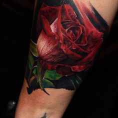 Realistic style rose tattoo on the right upper arm.