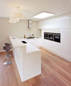 pur weiße Küche in U-Form mit Holzbodenbelag