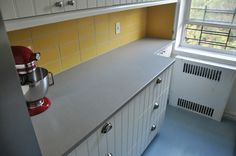 """Our (almost) finished kitchen renovation. Still need to paint trim and replace blinds. IKEA Sektion cabinets with Hittarp fronts. Forbo Marmoleum Click flooring in Sky Blue. Heath Ceramics tile backsplash in Stone Gold from the Classic Field line, 4x8"""". Caesarstone countertops in Raw Concrete."""