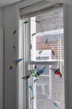 Flying Birds Mobile, four multi colored stained glass birds floating under leaf covered branches. $72.00, via Etsy.
