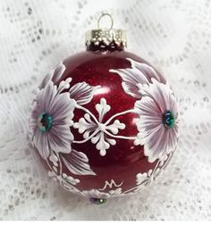 Red metallic glass ornament with White 3D texture painted MUD design with multi-colored rhinestone flower centers. Each ornament I create is a one-of-a-kind. The texture medium and paint brush I use to paint the ornaments were both created to my specifications. My signature M is located on the bottom of the ornament. Gift boxed. Measures 3 x 3 Ornament weight is 2 ounces.