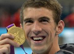 Michael Phelps poses with his gold medal from the 4x200-meter freestyle relay, the 19th medal of his Olympic career.