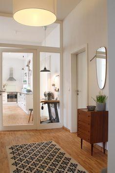 Flur – helle Farben, nur braunes Möbelstück und Teppich geben Farbe