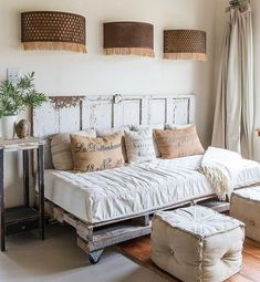 Farmhouse daybed made of pallets with an old door for a backboard. Love the poufs in front of it!