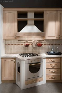 La bellissima zona cottura, con piano cottura e forno angolati su un blocco sporgente in muratura.