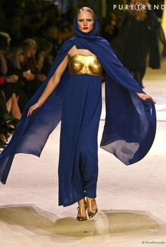 Yves Saint Laurent : a lapis and gold Claude Lalanne breastplate dress during the 2002 YSL finale retrospective.