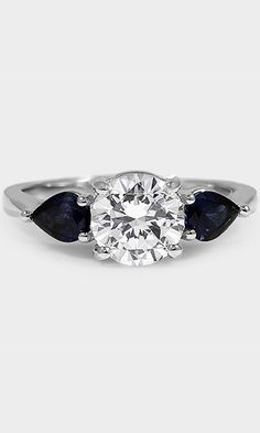 This classically styled three stone ring features two brilliant blue pear-shaped sapphires, which complement the gracefully elevated center diamond.