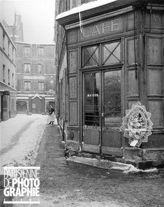 Ménilmontant. Le passage d'Eupatoria sous la neige, depuis le passage Notre-Dame-de-la-Croix. Au premier plan, à l'angle devant un café, une couronne mortuaire offerte par les habitants du quartier à l'occasion de la mort d'un enfant. Paris (XXème arr.), 1948. Photographie de René Giton dit René-Jacques (1908-2003).
