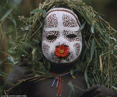This young child is shown with intricate face paint, a bright red flower in his mouth and strings of hand-strung beads. Images of the Omo Tribes in the Omo Valley, Ethiopia by Hand Silvester