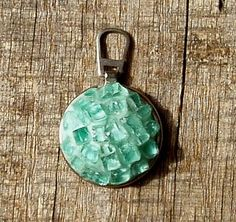 The metal ring and tab is from an old zipper pull, a pad of aqua colored polymer clay in the center, coated it with translucent liquid clay and pressed bits of broken windshield glass into it.