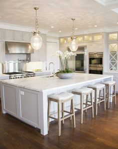 I like the very slight color difference between the white and gray cabinets. I like the glass cabinets, and I like the vent hood with small cabinets above. Don't love the pendant lights.