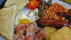 Engels ontbijt: geroosterd brood, roomboter, champignons, tomaat, spek, ei, worst, bloedworst, witte bonen in tomatensaus