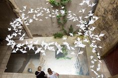 a team of designers has suspended dozens of crafted origami cranes from a courtyard ceiling, arranging them in a spiraling configuration overhead.