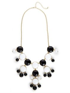 Glamour with a graphic twist — that's how we like to describe this stunning statement necklace. It features gorgeous cabochon gems, in cool ebony and ivory, in a lavish chandelier silhouette.