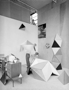 Charles Eames spinning a new toy of colored cardboard sections which are easily joined by a child to form odd shapes.