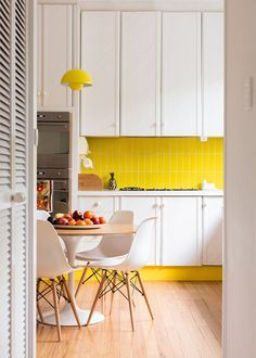 White kitchen with a yellow backsplash and pendant light